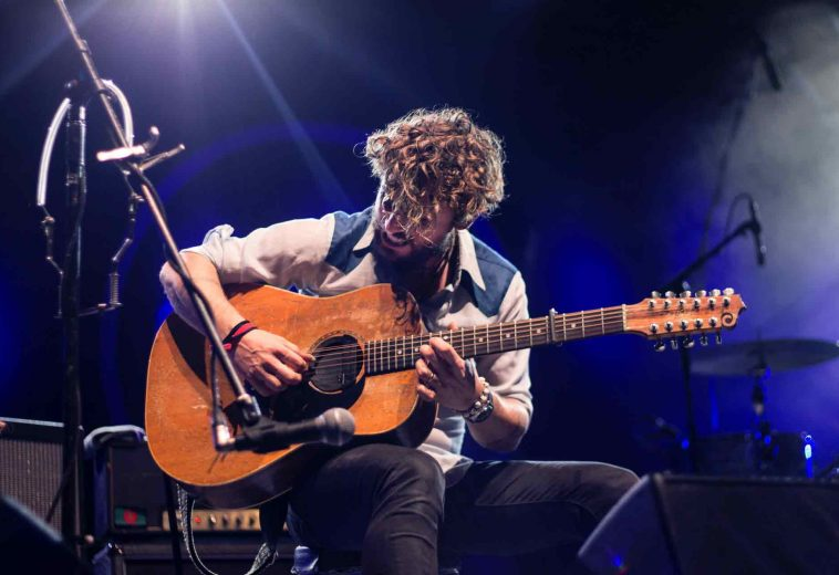 man-playing-guitar-sitting-on-chair-1425297