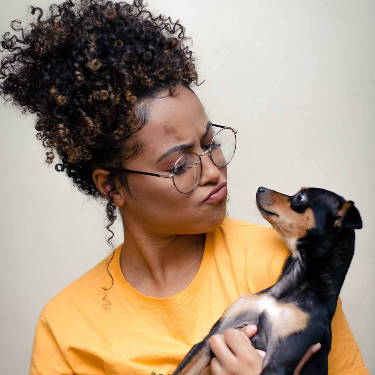 woman-holding-short-coated-black-and-brown-puppy-3190736
